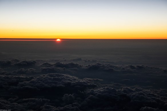the sun sets over the clouds